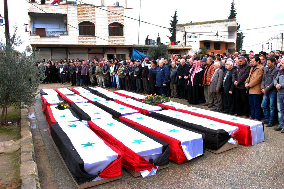 Photo - In this photo released by the Syrian official news agency SANA, Syrian citizens pray over the coffins wrapped by Syrian flags for the victims who were killed Thursday by a car bomb, during their funeral processions, at al-Kaffat village in the central Hama province, Syria, Friday, Jan. 10, 2014. Rebel-on-rebel fighting between an al-Qaida-linked group and an array of more moderate and ultraconservative Islamists has killed nearly 500 people over the past week in northern Syria, an activist group said Friday, in the most serious bout of violence among opponents of President Bashar Assad since the civil war began. (AP Photo/SANA)