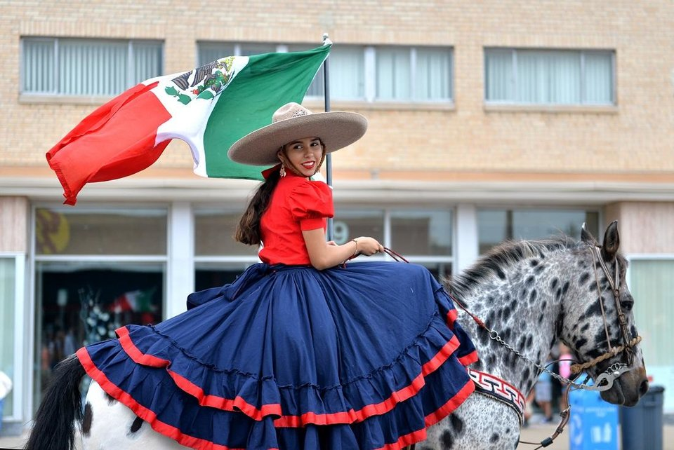 Photo - Wendy Sanchez rides a horse and carries the Mexican flag during the Fiesta de las America's in Oklahoma  City on September 29, 2018. This year's festival is going virtual due to the coronavirus pandemic. [The Oklahoman Archives]