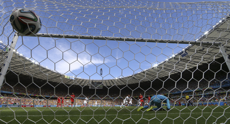Photo - Algeria's Sofiane Feghouli, center, scores from the penalty spot past Belgium's goalkeeper Thibaut Courtois, right, during the group H World Cup soccer match between Belgium and Algeria at the Mineirao Stadium in Belo Horizonte, Brazil, Tuesday, June 17, 2014.  (AP Photo/Hassan Ammar)