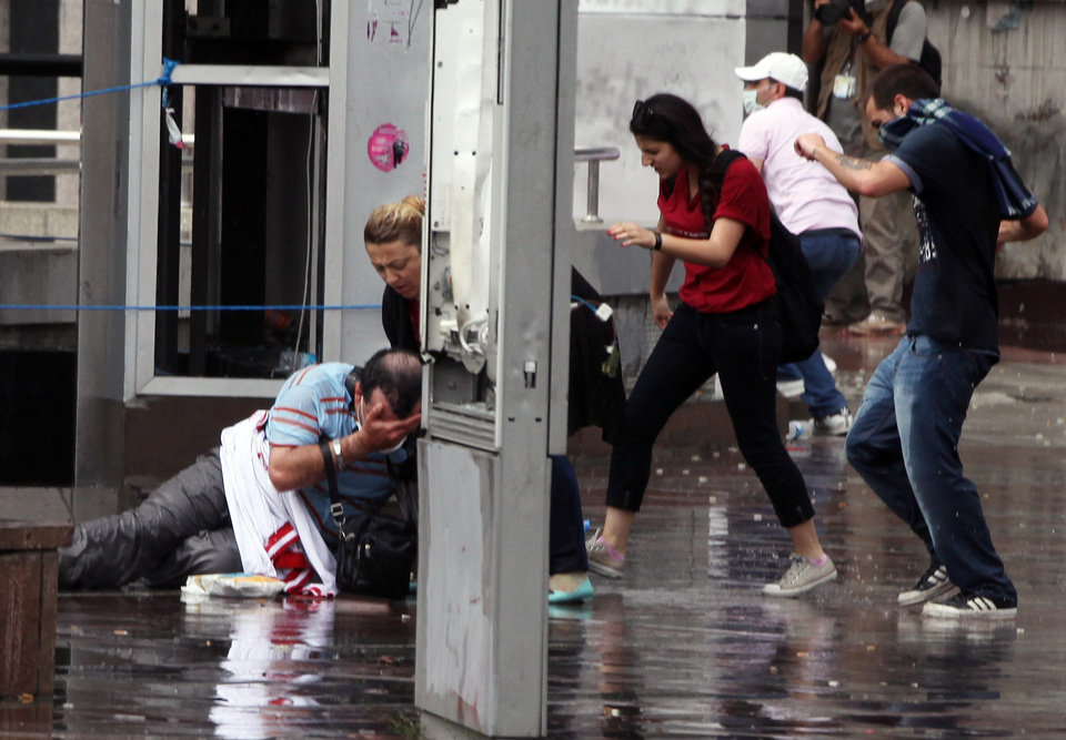 Photo - A man falls injured as Turkish riot police spray water cannon at demonstrators who remained defiant after authorities evicted activists from an Istanbul park, making clear they are taking a hardline against attempts to rekindle protests that have shaken the country, in city's main Kizilay Square in Ankara, Turkey, Sunday, June 16, 2013.(AP Photo/Burhan Ozbilici)