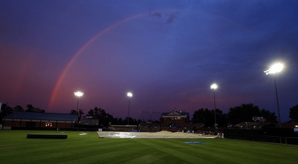 Photo - Crews remove a tarp covering the infield under a rainbow after a lightning delay paused the super regional between the University of Oklahoma Sooner (OU) softball team and Tennessee in the first game of the NCAA super regional at Marita Hynes Field on May 23, 2014 in Norman, Okla. Photo by Steve Sisney, The Oklahoman