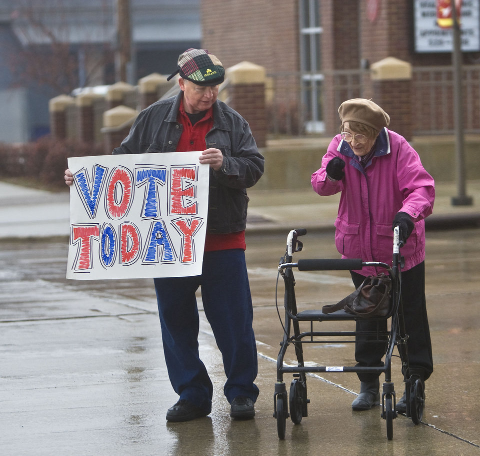 Mike Maloney briefly stops traffic so Elizabeth Rahn can cross the street to get to her polling place, outside the Rochester Senior Center, Tuesday, Nov. 6, 2012 in Rochester, Minn. Maloney was encouraging people to vote. (AP Photo/The Post-Bulletin, Jerry Olson)