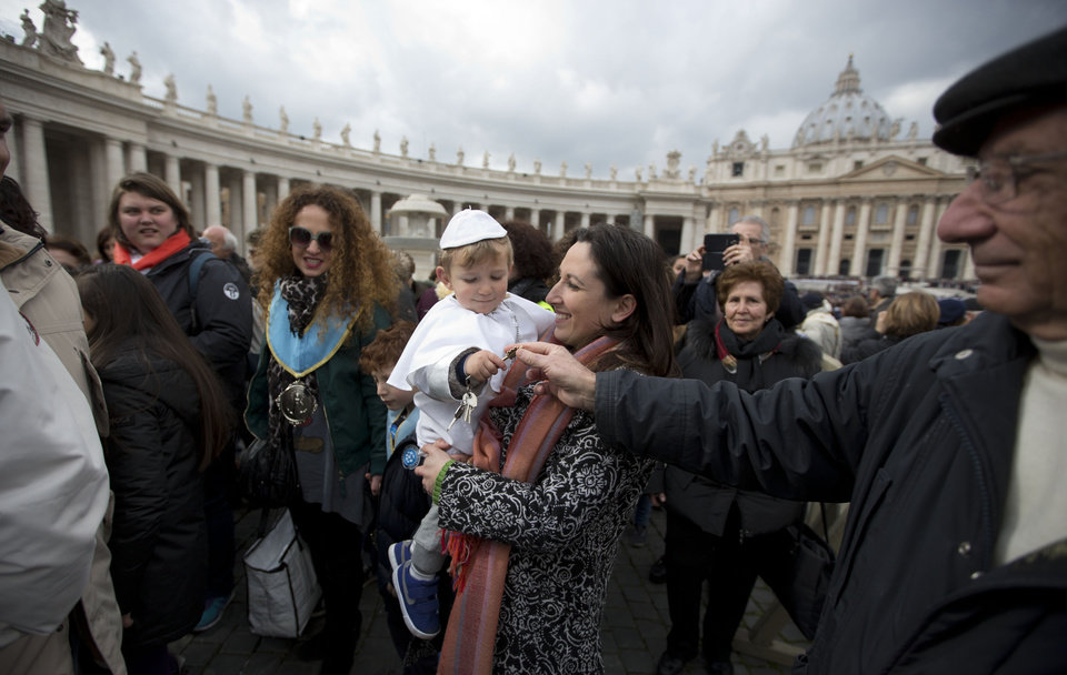 Photo - Paola Ciabattini holds up her 19-month-old son Daniele De Sanctis, dressed up as a pope, during Pope Francis' weekly general audience in St. Peter's Square at the Vatican, Wednesday, Feb. 26, 2014. Francis kissed the child as the new must-have Carnival costume made its debut at the pope's general audience Wednesday. Daniele, who was crying, was hoisted up to Francis as he drove by in his open-topped jeep. During Carnival in Italy, children often go to school and spend their weekends dressed up in pirate, princess — and now pope — costumes. Carnival, also known as mardi gras, marks the period before the church's solemn Lenten season begins. Ciabattini said she dressed her son as a pope in a demonstration of affection towards Pope Francis. (AP Photo/Alessandra Tarantino)