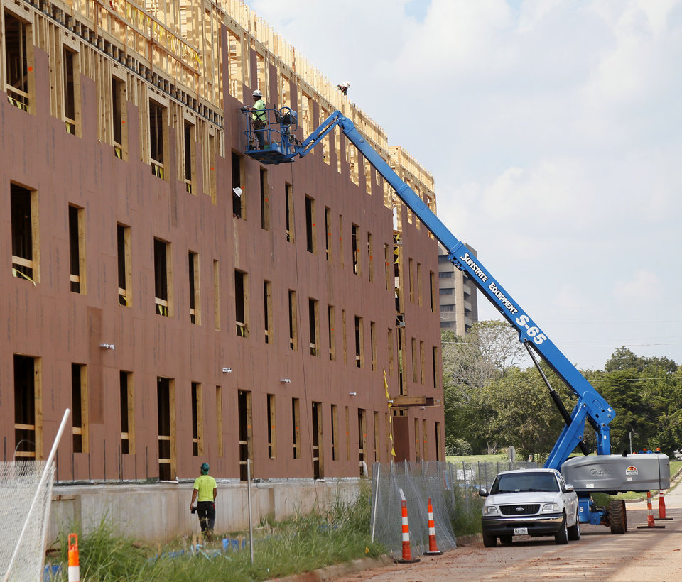Photo -  Construction of new affordable apartments is well underway immediately east of the historic Page Woodson School, which also is being renovated into housing and community space. [Photo by Nate Billings, The Oklahoman]