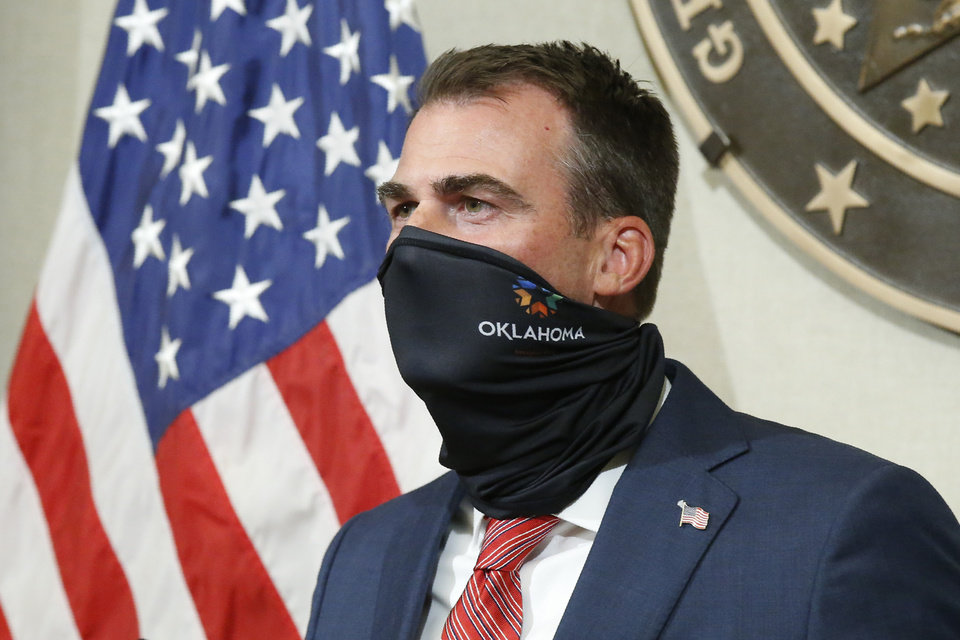 Photo - Oklahoma Gov. Kevin Stitt demonstrates how easy it is to wear a face mask during a news conference, Tuesday, June 30, 2020, in Oklahoma City. Stitt encouraged Oklahomans to wear a face mask, but said that he will not consider placing a face mask mandate on Oklahoma. (AP Photo/Sue Ogrocki)