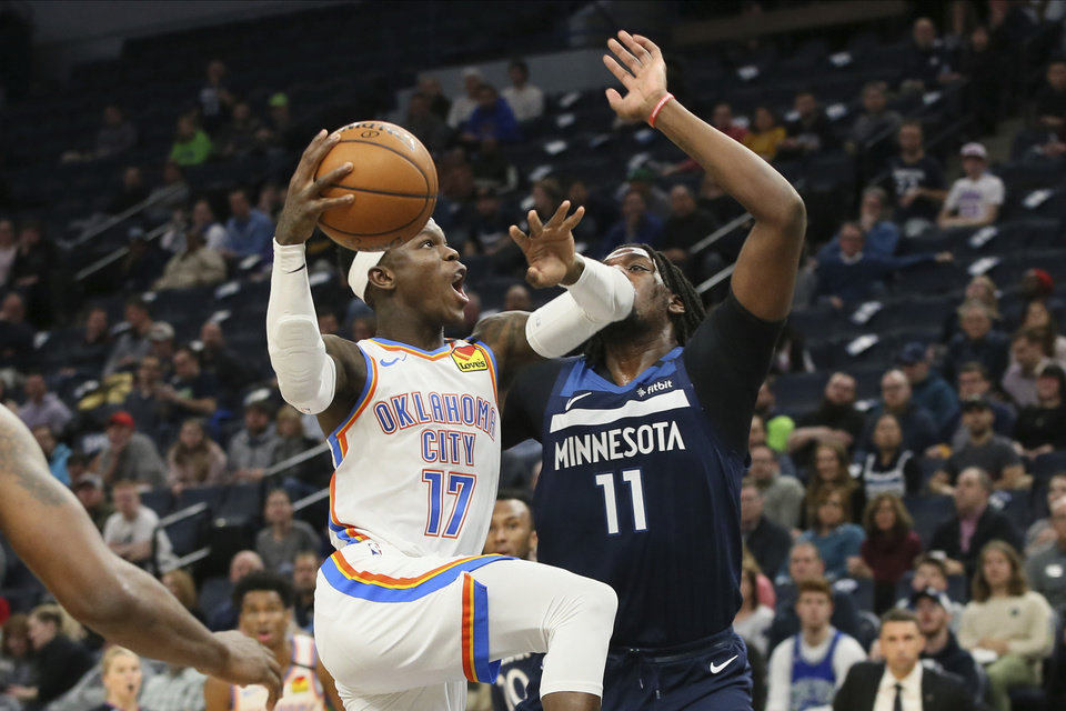 Photo - Oklahoma City Thunder's Dennis Schroder, left, of Germany, eyes the basket as Minnesota Timberwolves' Naz Reid defends in the second half of an NBA basketball game Monday, Jan. 13, 2020, in Minneapolis. The Thunder won 117-104. Reid came off the bench to score 20 points. (AP Photo/Jim Mone)