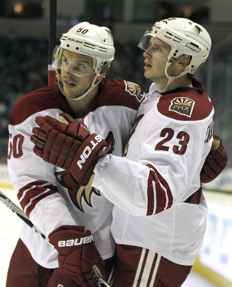Phoenix Coyotes defenseman Oliver Ekman-Larsson (23) celebrates  Antoine Vermette (50) after scoring a goal against the San Jose Sharks during the second period an NHL hockey game in San Jose, Calif., Saturday, Oct. 5, 2013. (AP Photo/Tony Avelar)
