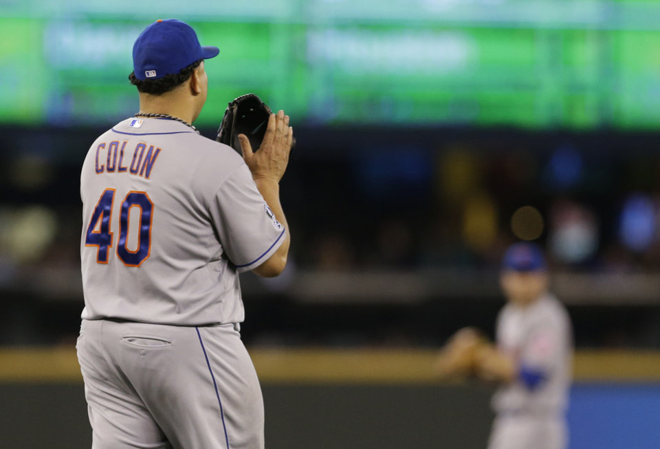 Photo - New York Mets starting pitcher Bartolo Colon claps his hand on his mitt in the seventh inning after Seattle Mariners' Robinson Cano hit a single to break up what had been a perfect game for Colon, Wednesday, July 23, 2014 in Seattle. (AP Photo)