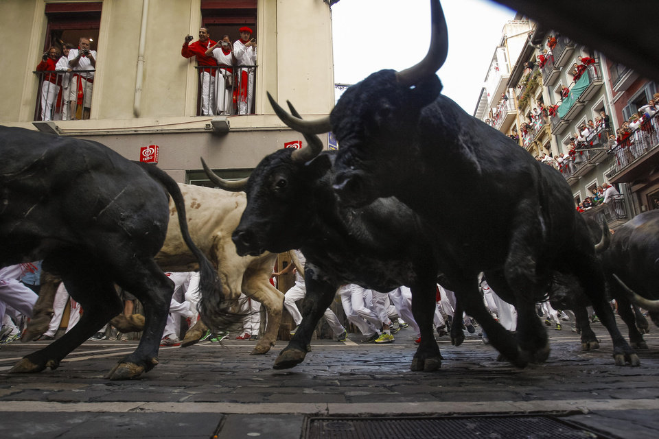 Photo - Dolores Aguirre fighting bulls and revelers run during the running of the bulls of the San Fermin festival, in Pamplona, Spain, Tuesday, July 8, 2014. Revelers from around the world in Pamplona take part in an eight-day event of the running of the bulls glorified by Ernest Hemingway's 1926 novel