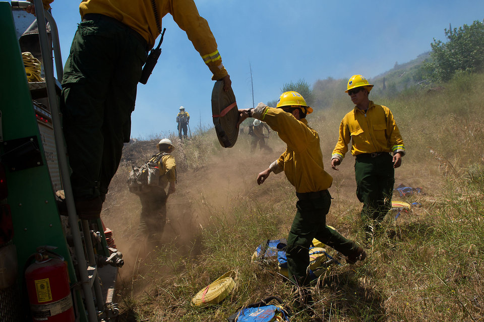Photo - U.S. Forest Service fire crews lay hose north of Highway 50 in El Dorado County, Calif. on Tuesday, July 9, 2013. More than 800 personnel are working a wildland blaze today near Kyburz, Calif., that is 40 percent contained. Despite progress overnight, the fire burning near Kyburz in the Eldorado National Forest is still restricting travel through the Sierra on Highway 50. The California Department of Transportation is reporting today that one-way alternating controlled traffic is being let through on Highway 50 from about five miles east of Riverton to about 2 miles west of Kyburz near the wildland fire. (AP Photo/The Sacramento Bee, Randall Benton)  MAGS OUT; LOCAL TV OUT (KCRA3, KXTV10, KOVR13, KUVS19, KMAZ31, KTXL40); MANDATORY CREDIT