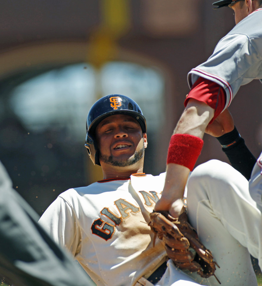 Photo - San Francisco Giants' Gregor Blanco is tagged out on a steal attempt at third base by Cincinnati Reds' Todd Frazier during the fourth inning of a baseball game, Sunday, June 29, 2014, in San Francisco. (AP Photo/George Nikitin)
