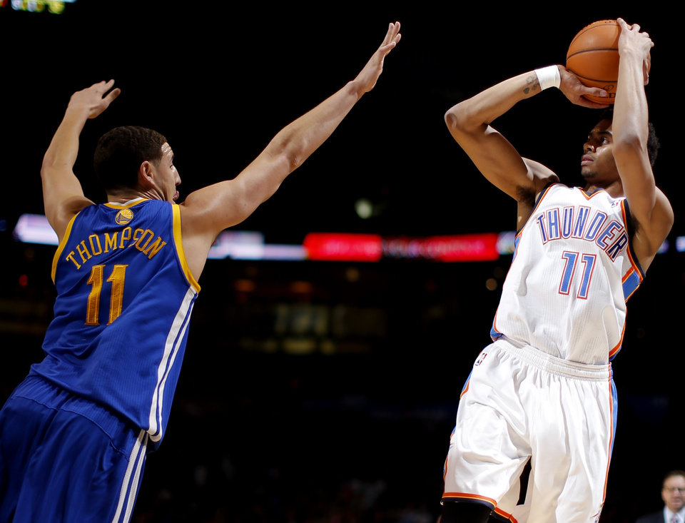 Photo - Oklahoma City's Jeremy Lamb shoots the ball over Golden State's Klay Thompson during an NBA basketball game between the Oklahoma City Thunder and the Golden State Warriors at Chesapeake Energy Arena in Oklahoma City, Friday, Jan. 17, 2014. Photo by Bryan Terry, The Oklahoman