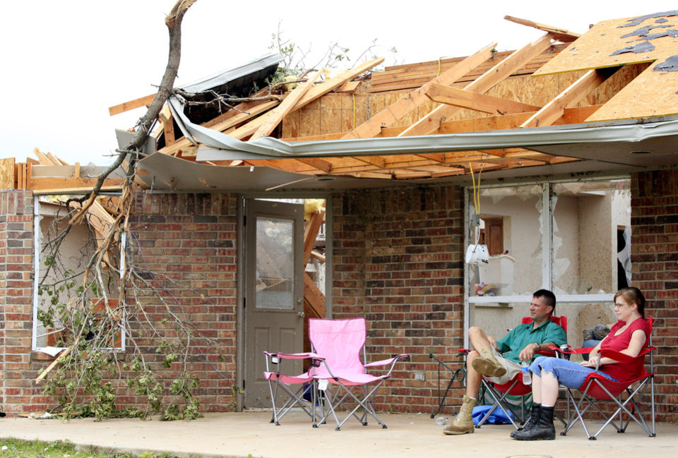 Photo - Steven and Erin Blair take a break from salvaging their belongings on the back patio of their home in the Deerfield Estates addition south of I-40 and Choctaw Rd Tuesday, May 11, 2010. A tornado Monday evening damaged or destroyed numerous homes in the neighborhood. Photo by Jim Beckel, The Oklahoman.