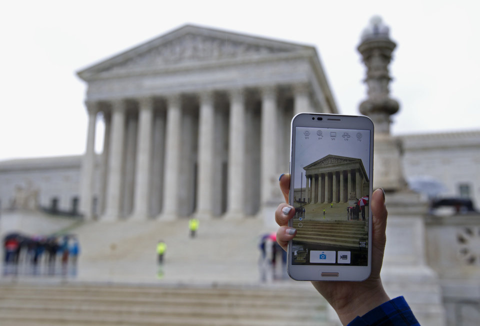 Photo - A Supreme Court visitor takes pictures with her cell phone outside the Supreme Court in Washington, Tuesday, April 29, 2014, during a hearing. The Supreme Court is considering whether police may search cellphones found on people they arrest without first getting a warrant. ( AP Photo/Jose Luis Magana)