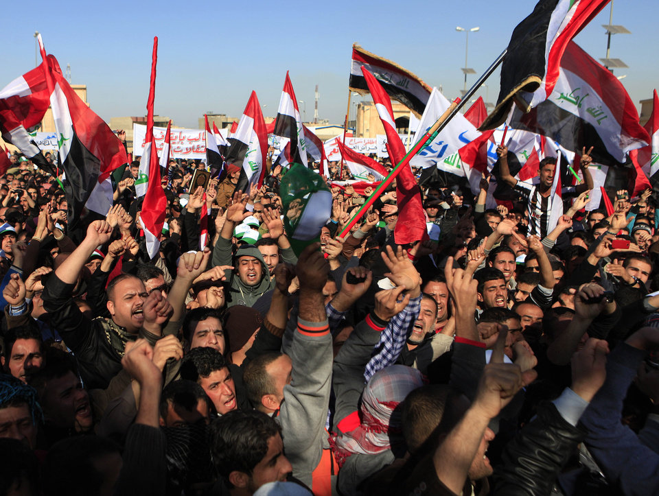 Protesters chant slogans against Iraq's Shiite-led government as they wave national flags during a demonstration in Baghdad, Iraq, Friday, Jan. 11, 2013. Thousands of protesters took to the street in western Anbar province and other predominantly Sunni areas in Iraq to protest what they believe to be the second-class treatment of Sunnis by the Shiite-led government. (AP Photo/Karim Kadim)