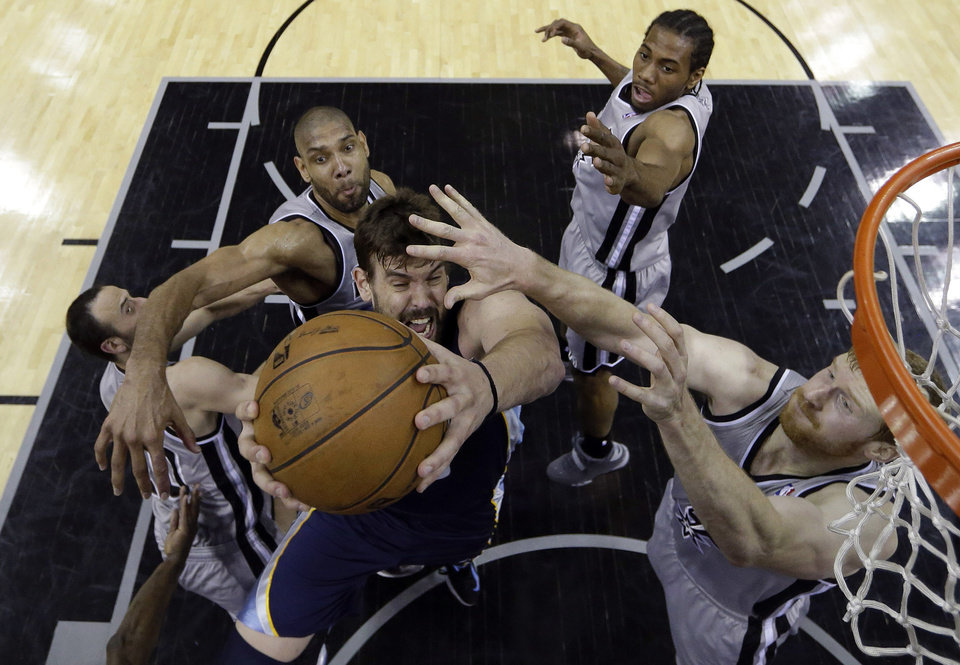 Photo - Memphis Grizzlies' Marc Gasol, center, is defended, from left, by San Antonio Spurs' Manu Ginobili, Tim Duncan, Kawhi Leonard, and Matt Bonner during the first half in Game 1 of a Western Conference Finals NBA basketball playoff series, Sunday, May 19, 2013, in San Antonio. (AP Photo/Eric Gay)
