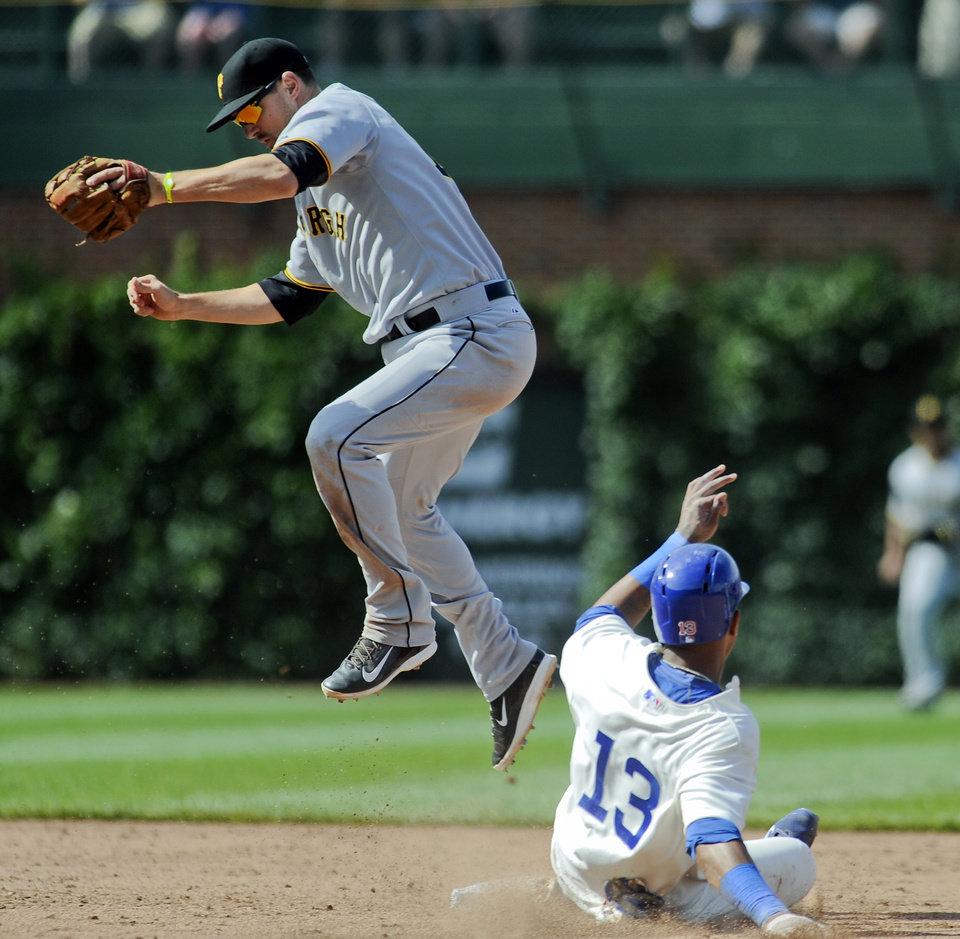 Photo - Chicago Cubs shortstop Starlin Castro (13) is tagged out at second base by Pittsburgh Pirates shortstop Jordy Mercer during the ninth inning of a baseball game, Sunday, June 22, 2014, in Chicago. (AP Photo/Matt Marton)