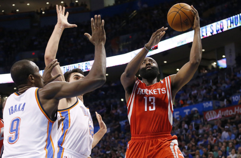 Photo - Houston Rockets guard James Harden (13) shoots in front of Oklahoma City Thunder forward Serge Ibaka (9) and center Steven Adams (12) during the second quarter of an NBA basketball game in Oklahoma City, Tuesday, March 11, 2014. Oklahoma City won 106-98. (AP Photo/Sue Ogrocki)
