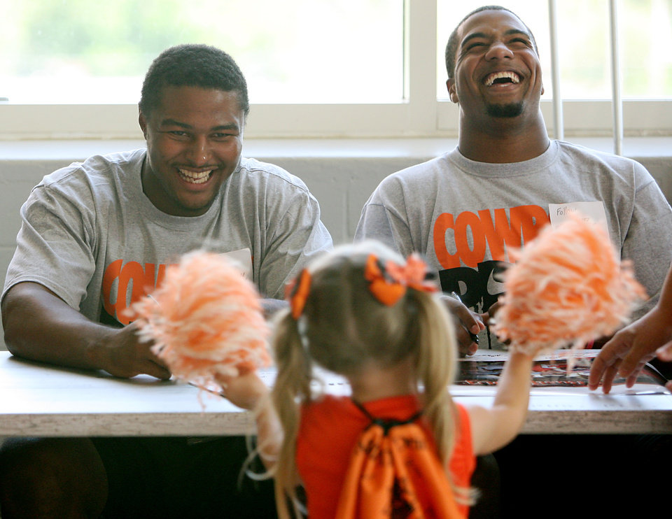 Photo - OSU players Justin Horton (left) and Tracy Moore (right) laugh as four-year-old Savannah Rendon, of Stillwater, does a cheer for them during Oklahoma State's Fan Appreciation Day at Gallagher-Iba Arena in Stillwater, Oklahoma on Saturday, Aug. 6, 2011. Photo by John Clanton, The Oklahoman ORG XMIT: KOD