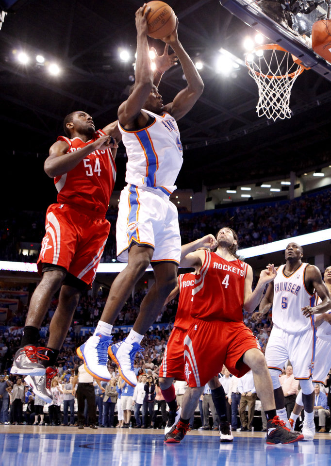Photo - Oklahoma City's Serge Ibaka (9)attempts a last-second shot as Houston's Patrick Patterson (54) and Luis Scola (4) defend during the NBA basketball game between the Oklahoma City Thunder and the Houston Rockets at the Chesapeake Energy Arena, Tuesday, March 13, 2012. Photo by Sarah Phipps, The Oklahoman.