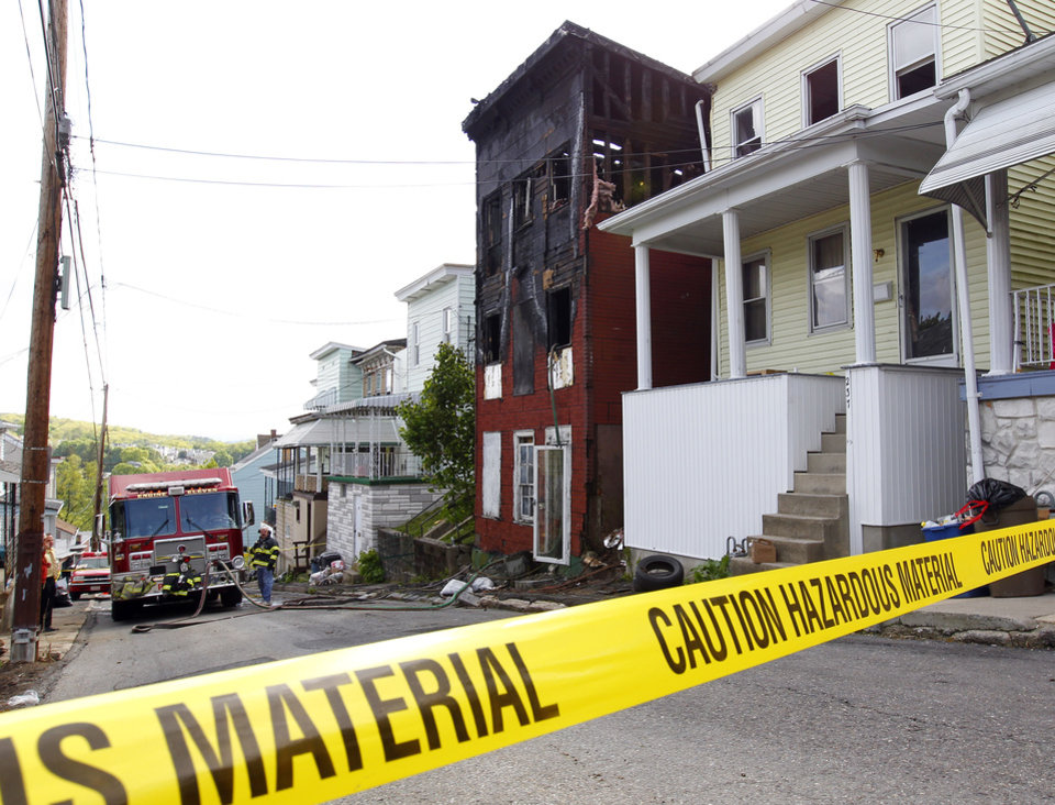 Photo - Caution tape blocks off the scene where two adults and four children were found dead early Monday, May 13, 2013, after a late night fire engulfed a home on Pierce Street in Pottsville, Pa. A fire marshal was sifting through the debris Monday and authorities were searching for the cause. (AP Photo/Rich Schultz)