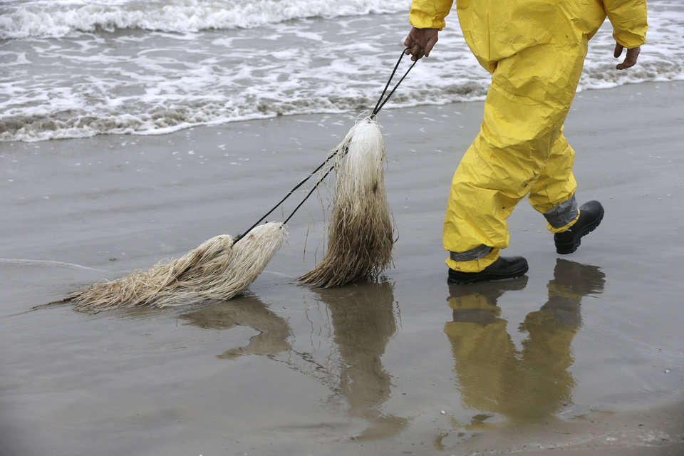 Photo - A worker drags viscous snare pom pons along East Beach in Galveston, Texas, to snag oil Monday, March 24, 2014. Thousands  of gallons of tar-like oil spilled into the major U.S. shipping channel after a barge ran into a ship Saturday. (AP Photo/Pat Sullivan)