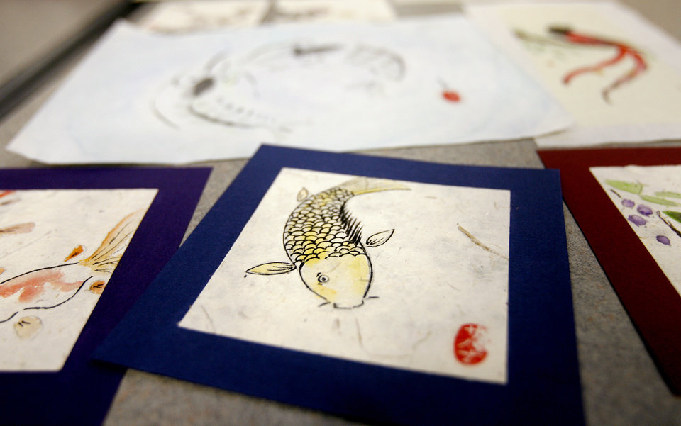 Photo - ART: Savannah Mitchell displays some of her artwork for the students to look at during her Chinese Brush Painting class at the Edmond Library in Edmond, Okla. Tuesday, July 14, 2009.  Photo by Ashley McKee, The Oklahoman   ORG XMIT: KOD