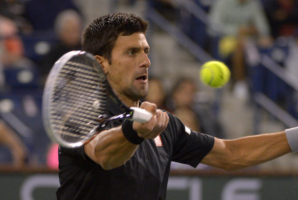 Photo - Novak Djokovic, of Serbia, returns a shot to Marin Cilic, of Croatia, during their match at the BNP Paribas Open tennis tournament, Wednesday, March 12, 2014, in Indian Wells, Calif. (AP Photo/Mark J. Terrill)