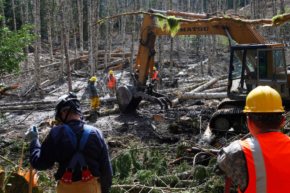 Photo - Workers look on as an excavator moves trees and dirt in the debris field, Wednesday, April 2, 2014, where volunteers continued to search through the mudslide area in Oso, Wash. (AP Photo/The Herald, Genna Martin)