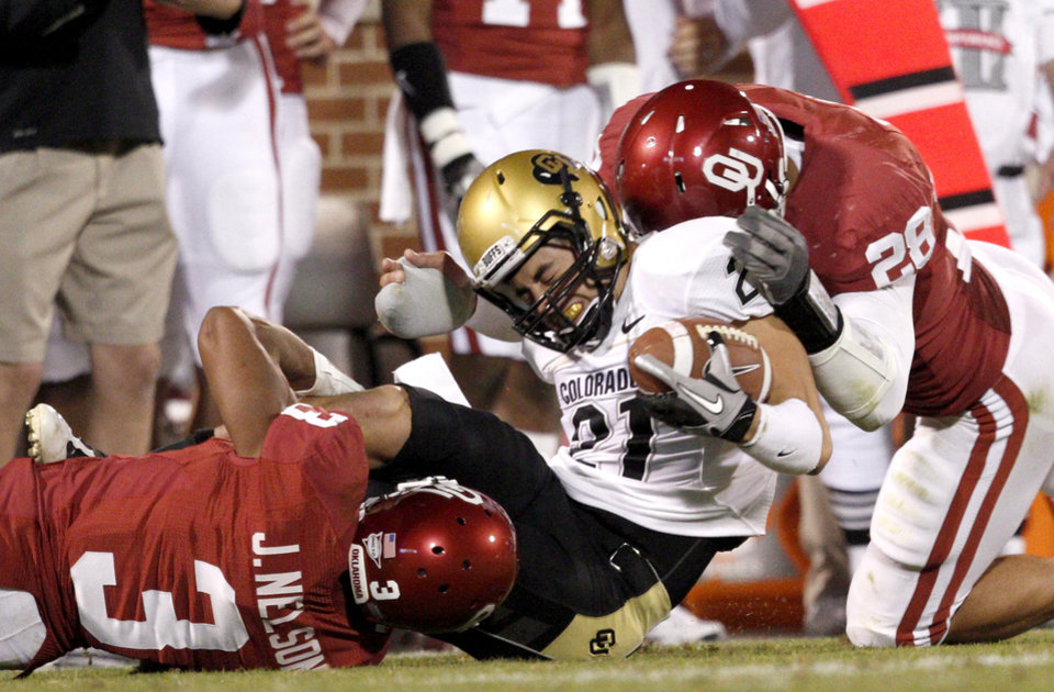 Photo - OU's Jonathan Nelson, left, and Travis Lewis bring down Colorado's Scotty McKnight during the college football game between the University of Oklahoma (OU) Sooners and the University of Colorado Buffaloes at Gaylord Family-Oklahoma Memorial Stadium in Norman, Okla., Saturday, October 30, 2010. Photo by Bryan Terry, The Oklahoman