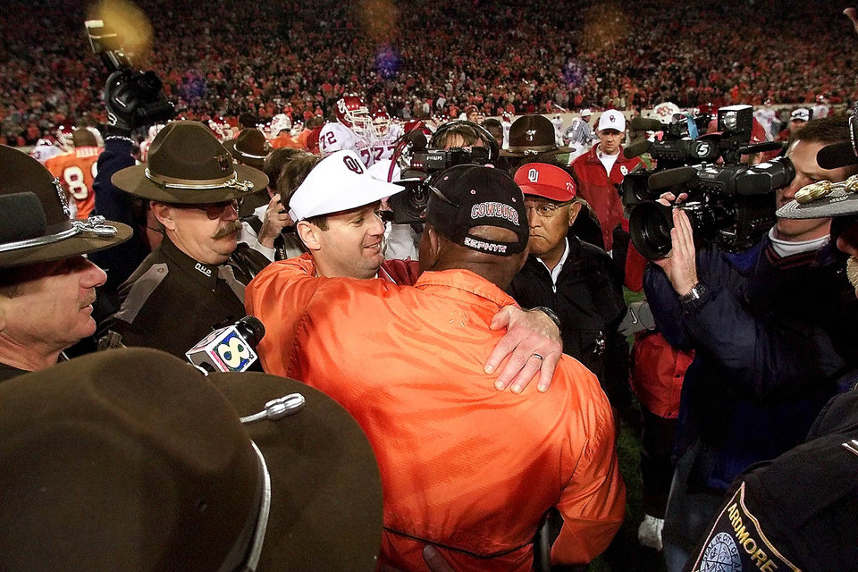Photo - OU vs OSU football in Stillwater. OU's coach Bob Stoops and OSU coach Bob Simmons embrace after the game. Staff Photo by Doug Hoke.