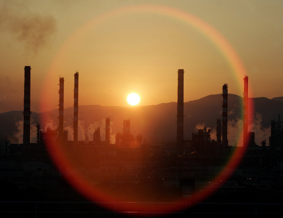 Photo - FILE - In this Tuesday, May 2, 2006, file photo, the sun sets over a oil refinery in Tarragona, Spain. In the 2000s, large investors in so-called clean technology wanted to finance companies that would help eliminate the world's dependence on oil, natural gas and coal. But in 2013, clean technology investment funds are not trying to replace the fossil fuel industry, they're trying to help it by financing companies that can make mining and drilling less dirty.( AP Photo/Manu Fernandez)