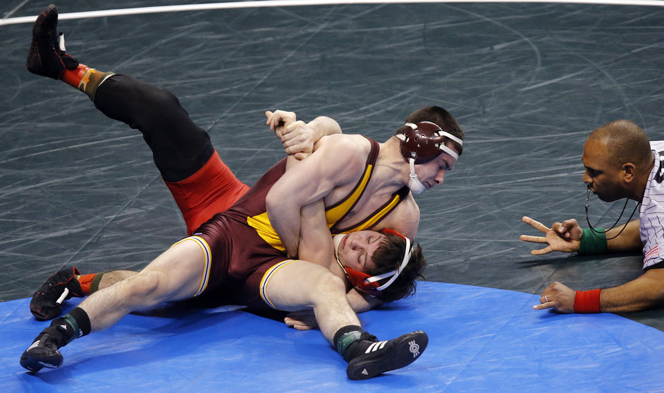 Photo - Central Michigan's Zach Horan , top, takes on Cornell's Michael Nevinger in the 141 pound match during the 2014 NCAA Div. 1 Wrestling Championships at Chesapeake Energy Arena in Oklahoma City, Okla. on Thursday, March 20, 2014. Photo by Chris Landsberger, The Oklahoman