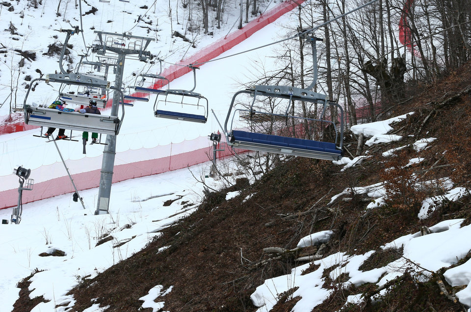 Photo - An inter-mingling of snow and brown patches are seen near the alpine course at the Sochi 2014 Winter Olympics, Tuesday, Feb. 11, 2014, in Krasnaya Polyana, Russia. Warm temperatures in the mountains made the snow too soft and caused the cancellation of Women's downhill training on Tuesday.  (AP Photo/Alessandro Trovati)
