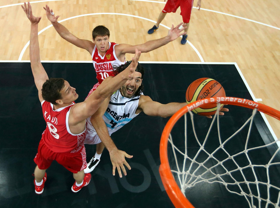 Argentina's Luis Scola (4) drives to the basket against Russia's Alexander Kaun (8) during the men's bronze medal basketball game at the 2012 Summer Olympics  in London on Sunday, Aug. 12, 2012. (AP Photo/Christian Petersen, Pool)
