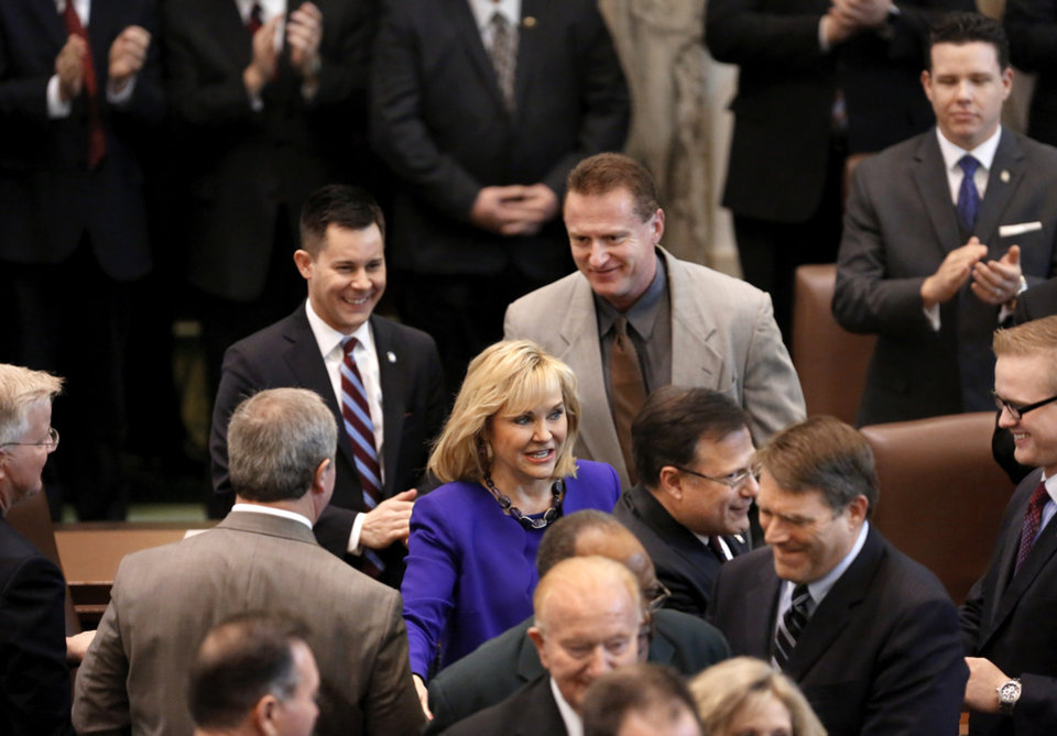 Photo - Surrounded by hospitable lawmakers, Gov. Mary Fallin smiles as she enters the House chamber and makes her way to the podium. Fallin outlined her goals for the upcoming legislative session during her state of the state speech to a joint session of the legislature in the House chamber at the state Capitol on Monday, Feb. 3, 2014.   Photo by Jim Beckel, The Oklahoman