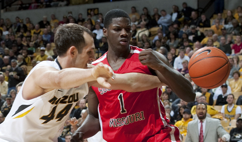 Photo - Missouri's Ryan Rosburg, left, and Southeast Missouri State's Nino Johnson, right, look for a rebound during the first half of an NCAA college basketball game Tuesday, Dec. 4, 2012, in Columbia, Mo. (AP Photo/L.G. Patterson)