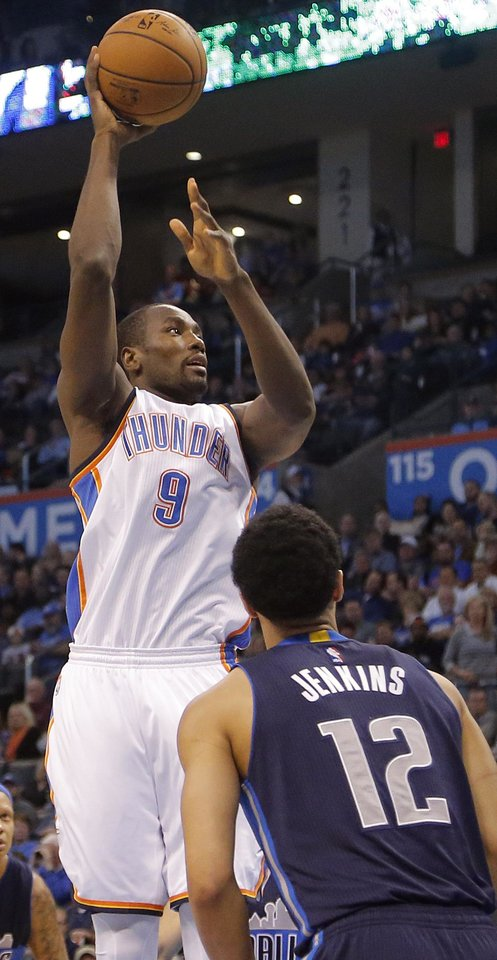 Photo - Oklahoma City's Serge Ibaka (9) shoots the ball over Dallas' John Jenkins (12) during the NBA basketball game between the Oklahoma City Thunder and the Dallas Mavericks at Chesapeake Energy Arena on Wednesday, Jan. 13, 2016, in Oklahoma City, Okla.  Photo by Chris Landsberger, The Oklahoman