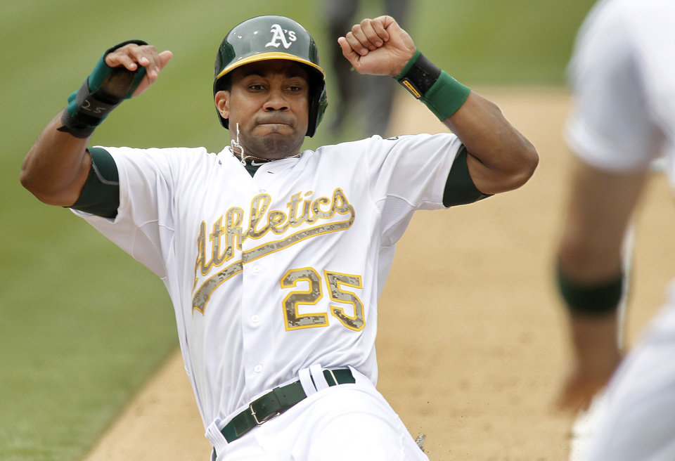 Photo - Oakland Athletics' Chris Young (25) slides into home plate after a Yoenis Cespedes doubled against the San Francisco Giants during the seventh inning of a baseball game in Oakland, Calif., Monday, May 27, 2013. (AP Photo/Tony Avelar)