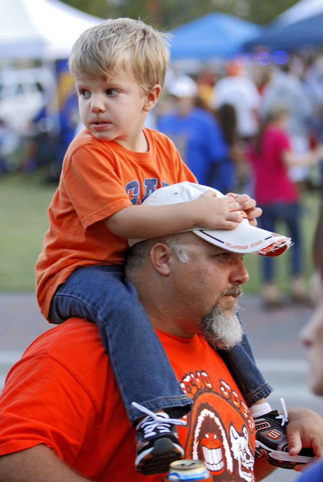 Todd Kirk, of Springdale, Ark., carries his son Konnor on his shoulders before the OSU-Tulsa game. Photo by Chris Landsberger, The Oklahoman