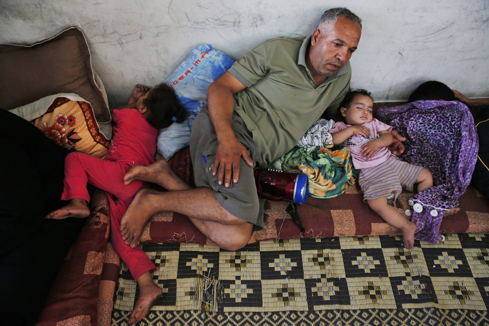 Photo - Palestinian Riyad Hamed, 47, center, sits as his daughter Ranin, 3, left, and his granddaughter Asmahan, 1, right, sleep in a classroom that they stay in at a United Nations school where dozens of families have sought refuge after fleeing their homes following heavy Israeli forces' strikes in Beit Hanoun, northern Gaza Strip, Saturday, July 19, 2014. Hamed and his immediate and extended family fled their homes three days earlier and have been staying at the school since. (AP Photo/Lefteris Pitarakis)