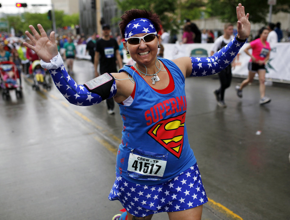 Photo - Tammy Pittman of Chickasha begins her run dressed as superman for the 14th Annual Oklahoma City Memorial Marathon in Oklahoma City, Sunday, April 27, 2014. The marathon was delayed over two hours beyond it's original start time of 6 a.m. Photo by KT King/The Oklahoman