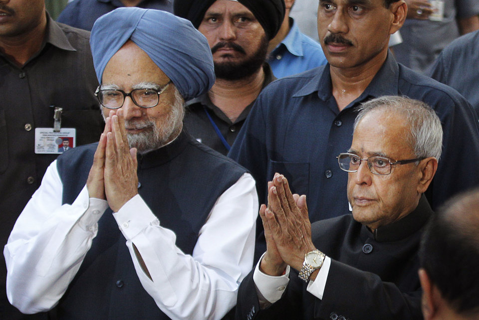 Photo -   India's President elect Pranab Mukherjee, right, and Indian Prime Minister Manmohan Singh, greet the media outside Mukherjee's residence in New Delhi, India, Sunday, July 22, 2012. The candidate from India's governing Congress party, former Finance Minister Pranab Mukherjee, was declared winner Sunday in the election for the country's next president, a largely ceremonial position. (AP Photo/ Manish Swarup)