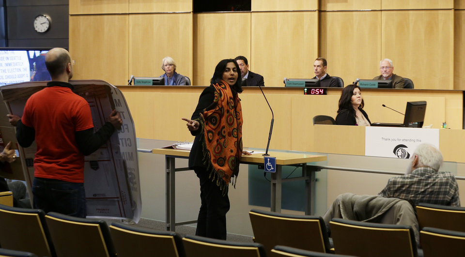 Photo - In this photo taken Nov. 4, 2013, Socialist candidate for Seattle City Council Kshama Sawant, center, speaks before the City Council about her support for raising the minimum wage to $15 an hour for all workers in the city. Sawant is challenging four-term Councilman Richard Conlin. (AP Photo/Ted S. Warren)