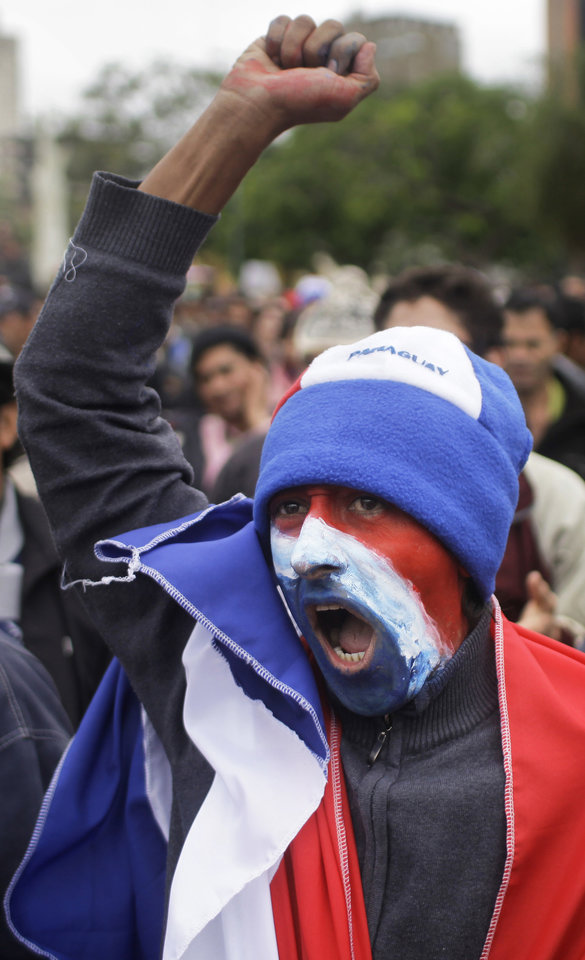 Photo -   A supporter of Paraguay's President Fernando Lugo, whose face is painted with the colors of Paraguay's national flag, protests against Lugo's impeachment trial, outside Parliament, in Plaza de Armas, Asuncion, Paraguay, Friday, June 22, 2012. Paraguayan lawmakers voted Thursday to impeach Lugo for his role in for his role in a deadly clash involving landless farmers and police. Lugo's trial was to begin Friday in Paraguay's Senate. (AP Photo/Jorge Saenz)