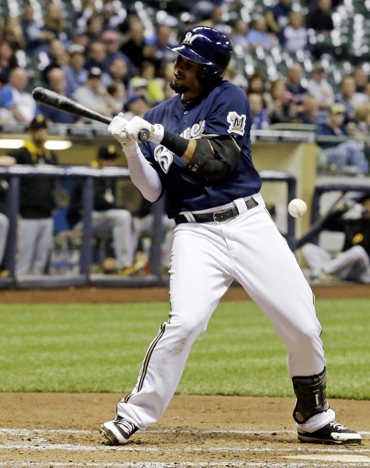 Photo - Milwaukee Brewers' Carlos Gomez is hit by a Pittsburgh Pirates' Gerrit Cole pitch during the third inning of a baseball game Tuesday, May 13, 2014, in Milwaukee. (AP Photo/Morry Gash)