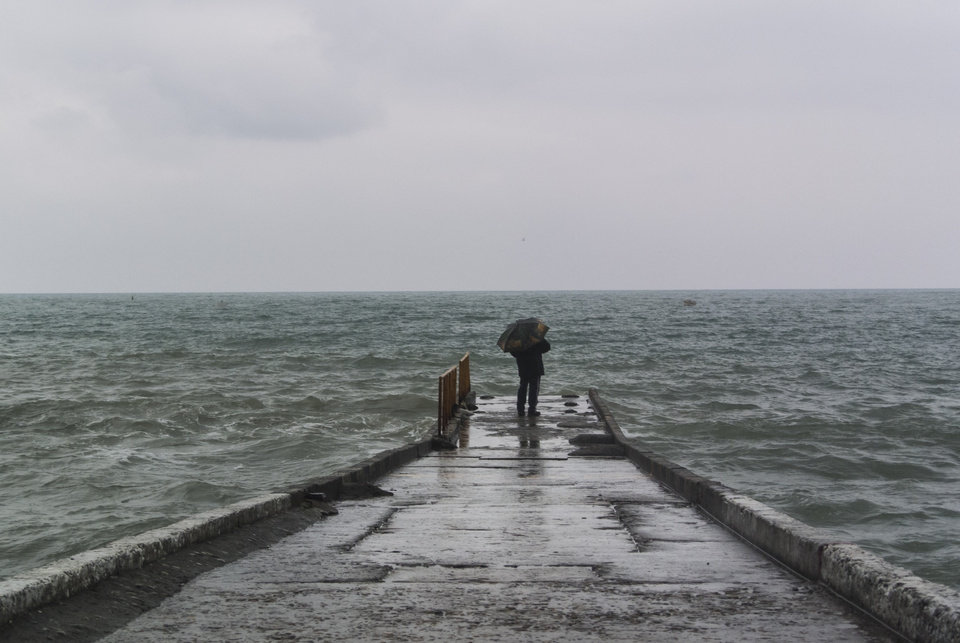 Photo - In this photo taken Thursday, Jan. 23, 2014, a man with an umbrella stands on the pier in central Sochi, Russia.  The Russian Black Sea resort of Sochi is hosting the Winter Games on Feb. 7-23.  (AP Photo/Nataliya Vasilyeva)