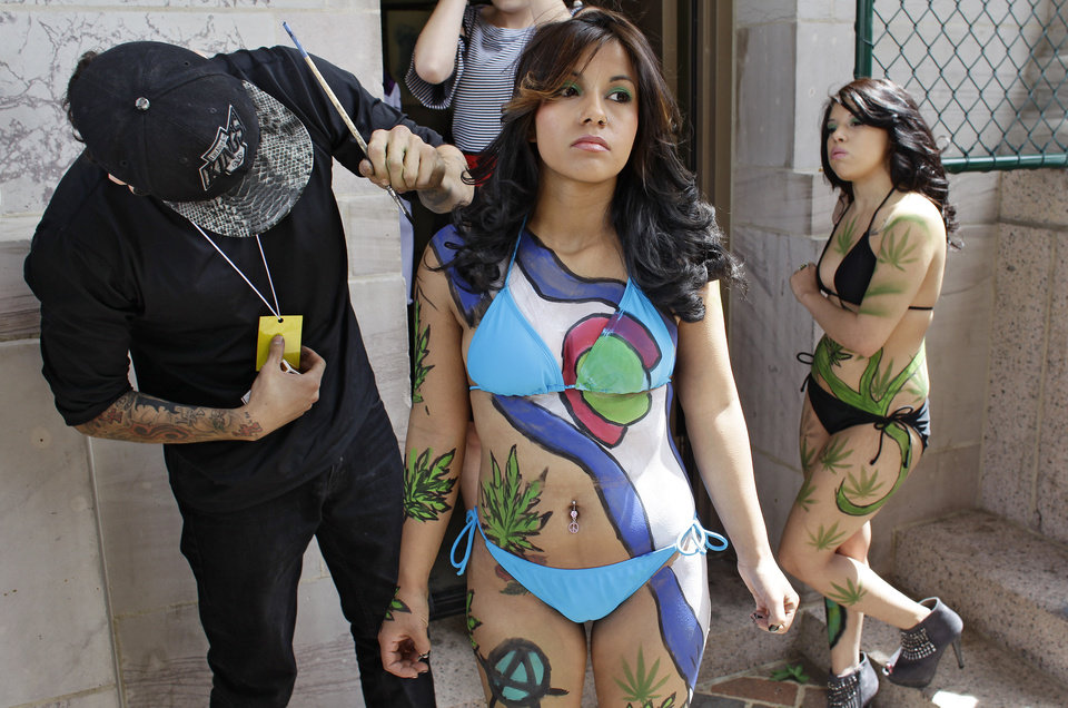 Photo - Tattoo artist Robert Duran touches up performer Ashley Lucero with a marijuana-themed body paint design, as Vanessa Pacheco looks on at right, at the Denver 4/20 pro-marijuana rally at Civic Center Park in Denver on Saturday, April 20, 2013. Even before the passage in November 2012 of Colorado Amendment 64 promised the legalization of marijuana for recreational use, April 20th has for years been a celebration of marijuana counterculture, with the 2013 Denver rally expected to draw larger crowds than previous years. (AP Photo/Brennan Linsley)