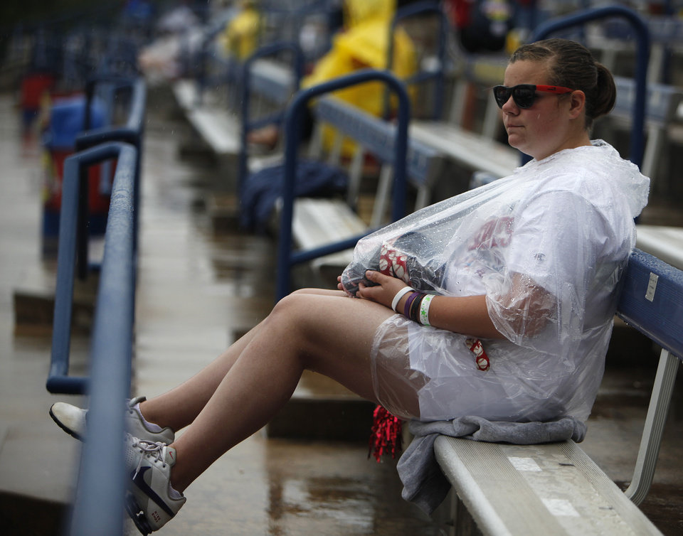 Morgan Smith, of Sioux Falls, S.D., sits in the rain at ASA Hall of Fame Stadium in Oklahoma City, Wednesday, June 6, 2012.  The final game of the Women's World College Series was delayed due to weather conditions.  Photo by Garett Fisbeck, The Oklahoman