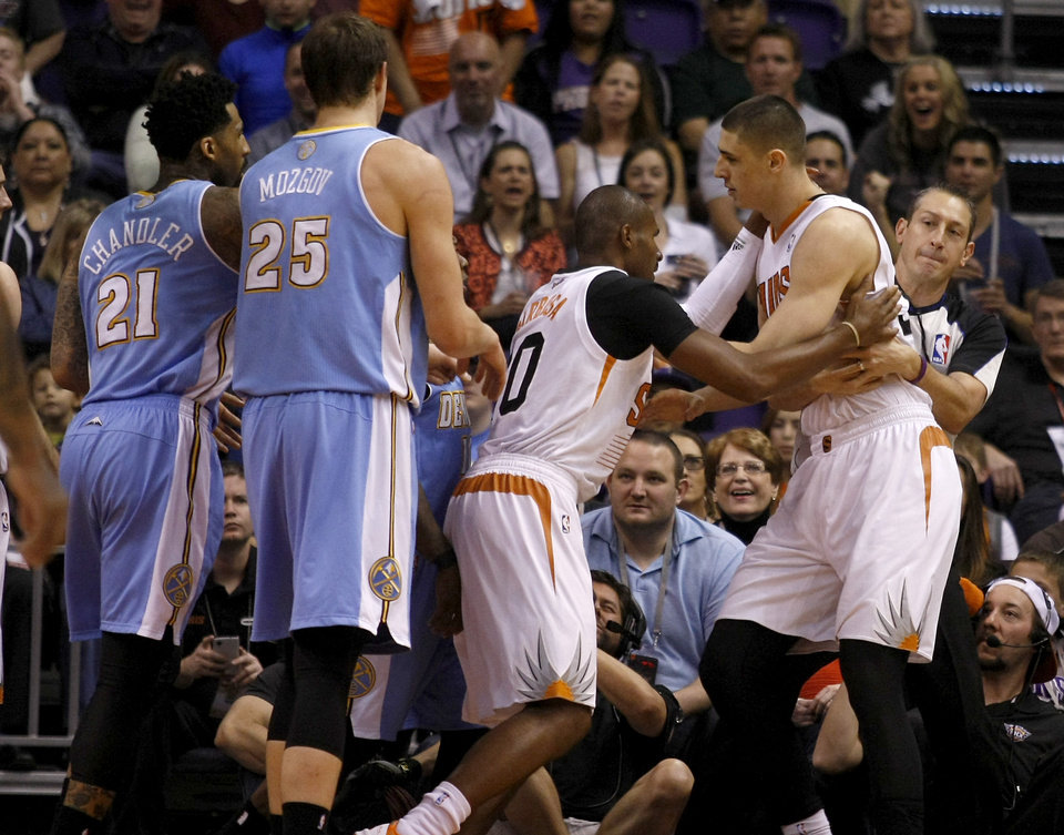 Photo - Phoenix Suns center Alex Len (21) gets held back from Leandro Barbosa (10) after getting into a shoving match with players of the Denver Nuggets in the first quarter during an NBA basketball game, Sunday, Jan. 19, 2014, in Phoenix. (AP Photo/Rick Scuteri)